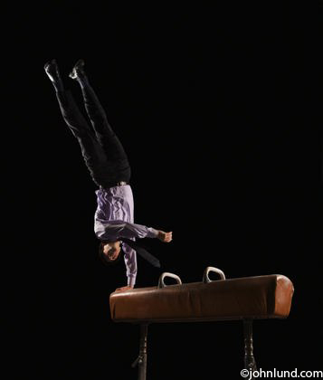Hispanic businessman dismounting from pommel horse while wearing business attire and showing skill and determination.